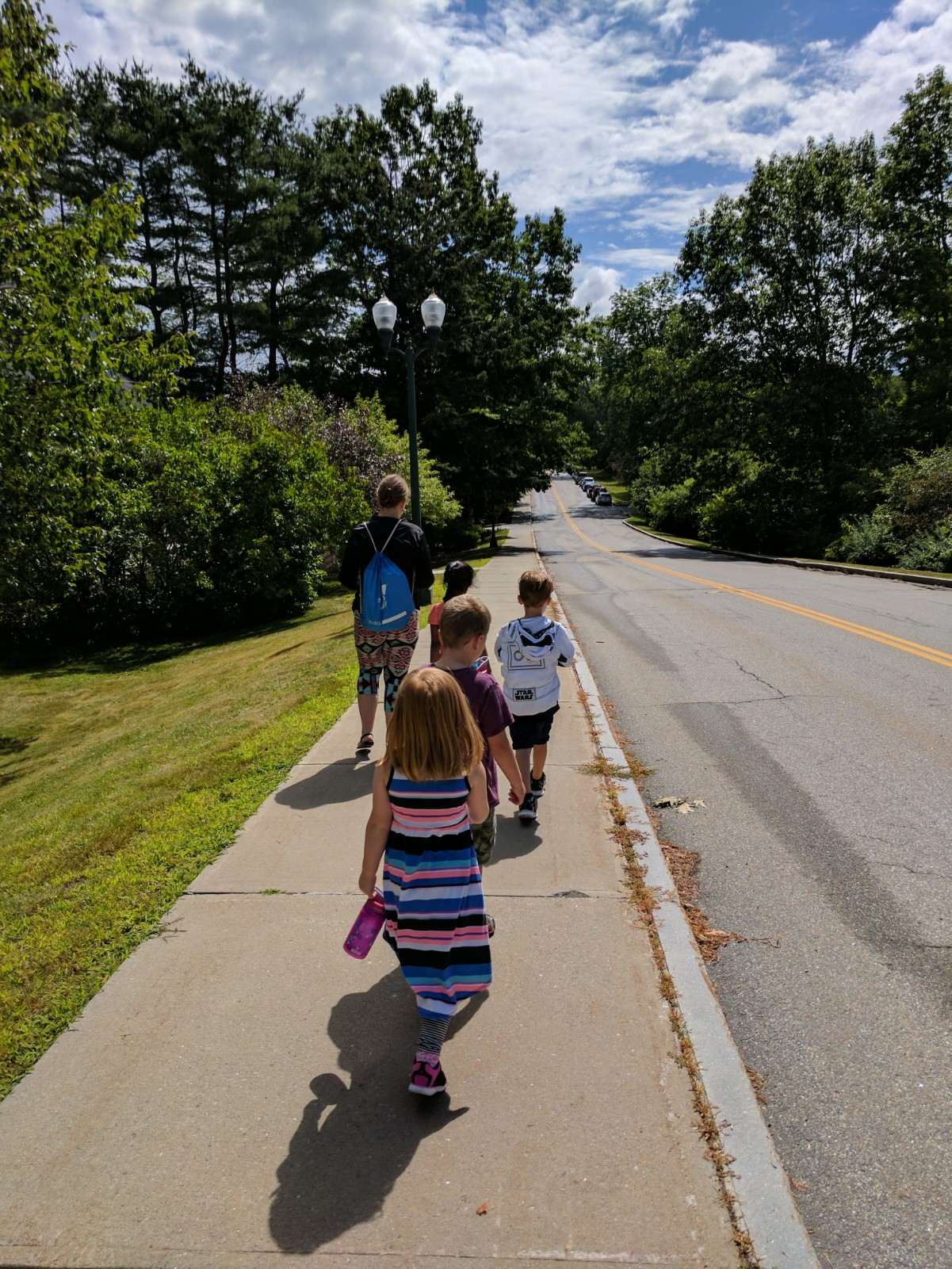 Kids walking on sidewalk with light pole